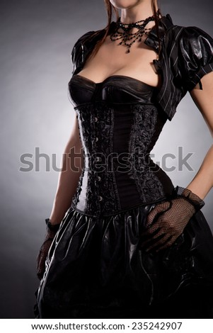 Beautiful young woman in Victorian style costume, studio shot on black background  - stock photo