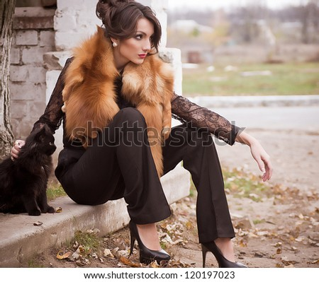 Beautiful young woman in vintage fashion clothes with cat - stock photo