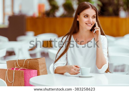 Beautiful young woman in white blouse talking on a mobile phone, drinking coffee and smiling while resting in cafe after doing shopping - stock photo
