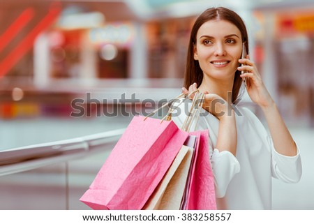 Beautiful young woman in white blouse talking on a mobile phone, holding shopping bags and smiling while standing in mall - stock photo