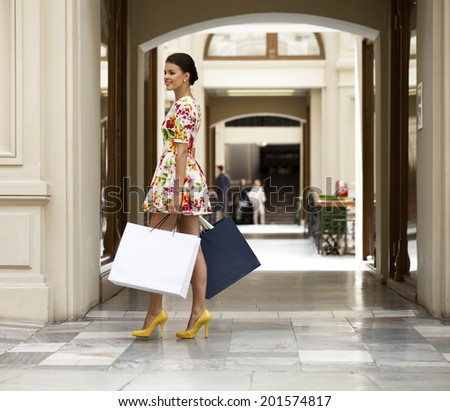 Beautiful young woman in white dress flowers walking in the shop - stock photo