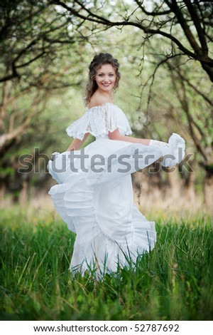 beautiful young woman in white dress is whirling - stock photo