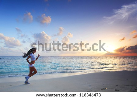 Beautiful young woman in white sportswear running on beach - stock photo