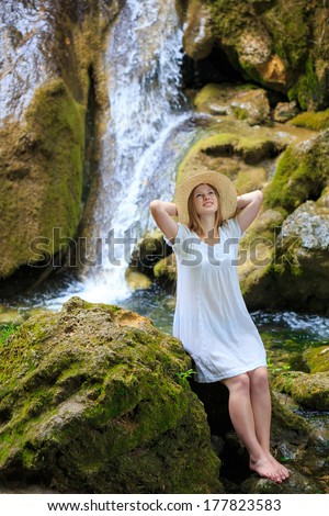 Beautiful young woman in white sundress and straw hat stopped to rest and dream near the waterfall among the mossy stones - stock photo