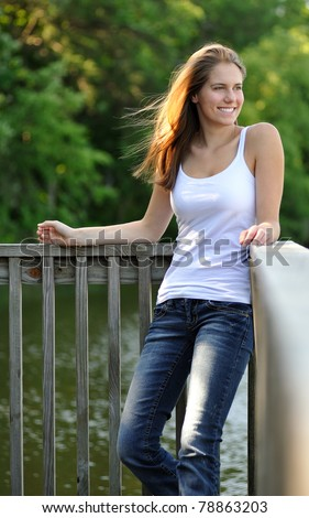 Beautiful young woman in white tank top leaning against a dock railing with morning sunlight highlighting her hair- blue jeans - smiling as she looks off frame - stock photo