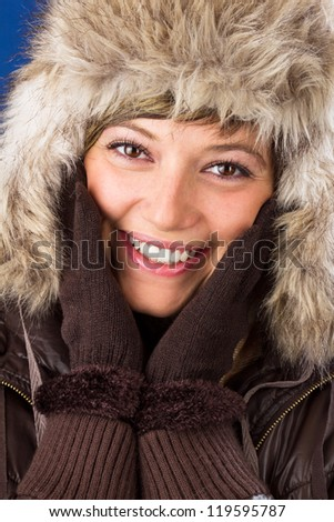 Beautiful young woman in winter clothes with a bright smile holding the hands to her face. Studio shot as a wintry close up portrait - stock photo