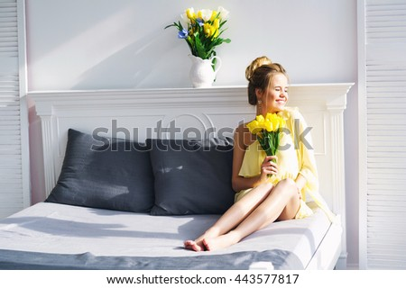 Beautiful young woman in yellow dress posing with bunch of fresh tulips on her bed in morning sunlight - stock photo