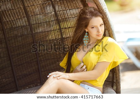 Beautiful young woman in yellow t-shirt and white shorts relaxing on chaise lounge near swimming pool  - stock photo