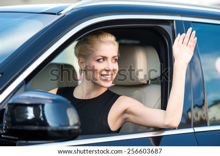 Beautiful young woman inside car driving it and waving. Concept for car rental  - stock photo