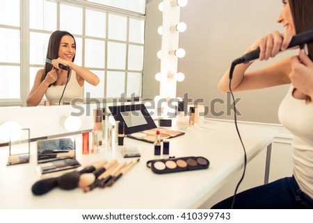 Beautiful young woman is doing her hair using a straightener and smiling while looking at the mirror - stock photo