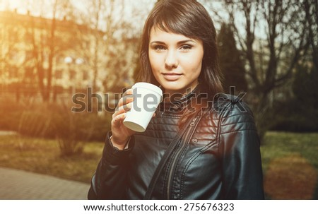 Beautiful young woman is drinking coffee outdoors. Invigorating morning. Stylish look - stock photo