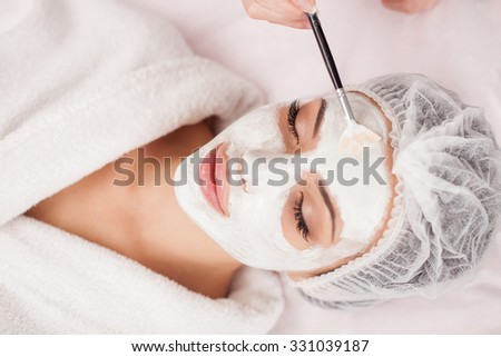 Beautiful young woman is getting facial mask at spa. She is lying and relaxing. Her eyes are closed with pleasure. The cosmetologist is applying cream on her face with brush - stock photo