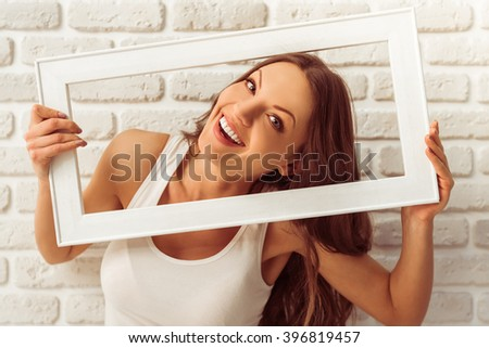 Beautiful young woman is holding a wooden frame, looking at camera and smiling, against white brick wall - stock photo