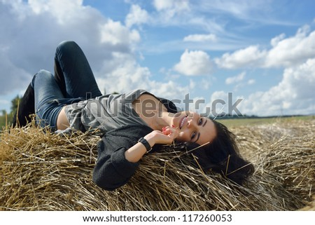 Beautiful young woman is lying on stack of hay on sunny day in the country - stock photo