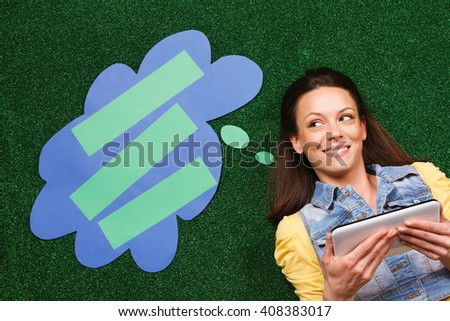 Beautiful young woman is lying on the grass and thinking about something while using digital tablet with a thought bubble beside her head. Woman thinking with thought bubble while using digital tablet - stock photo
