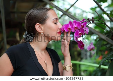 Beautiful young woman is smelling a pink orchid in a tropical garden - stock photo