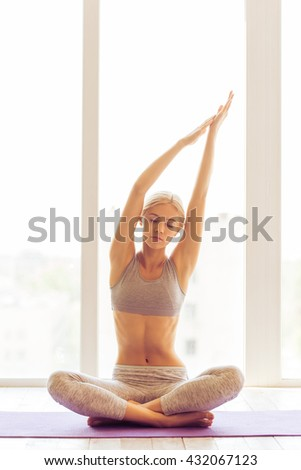 Beautiful young woman is stretching hands while meditating in lotus pose on yoga mat against window - stock photo