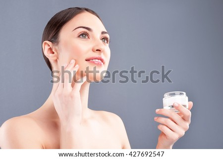 Beautiful young woman is treating her skin - stock photo