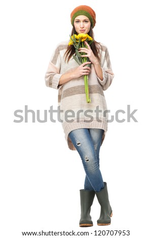 Beautiful young woman isolated on white background and holding yellow flowers in her hands. She is wearing a hat, gardening boots and looking at camera. - stock photo