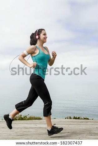 Beautiful young woman jogging on a boardwalk and listen music - stock photo