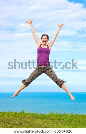 Beautiful young woman jumping and laughing by the ocean - stock photo