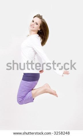 Beautiful young woman jumping into the air - stock photo