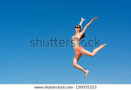 beautiful young woman jumping on a background of blue sky, having a fun time - stock photo
