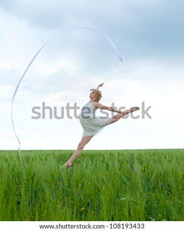 Beautiful young woman jumping on a green meadow with a gymnastic ribbon - stock photo