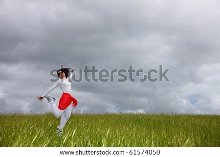 beautiful young woman jumping on field with a red scarf - stock photo