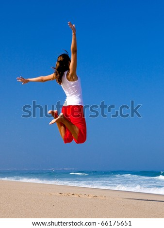 Beautiful young woman jumping on  the beach - stock photo