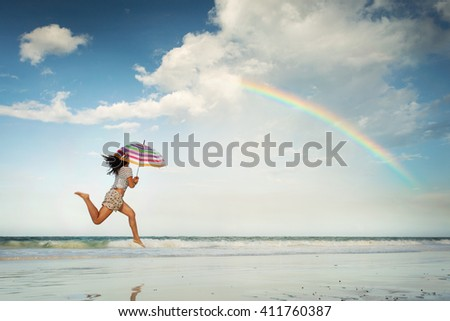 Beautiful young woman jumping on the beach with a colored umbrella with rainbow and white clouds in background