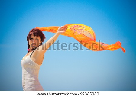 Beautiful young woman jumping over the blue sky with a colored tissue - stock photo