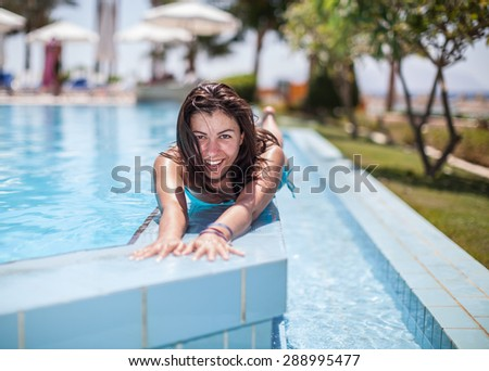 Beautiful young woman laying on the swimming pool wall, smiling and taking tan - stock photo