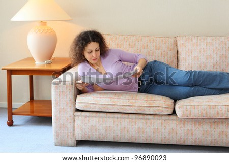 Beautiful young woman lies on couch in simple room and look at journal - stock photo
