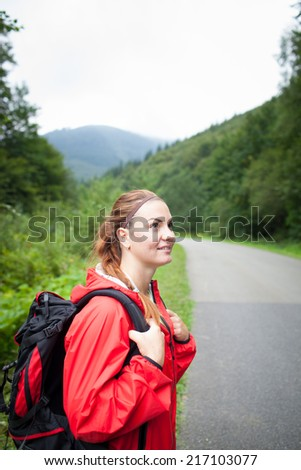 Beautiful young woman looking around and watching nature in natural park/on mountain  - stock photo