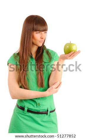 Beautiful young woman looking at a green apple, studio shot. - stock photo