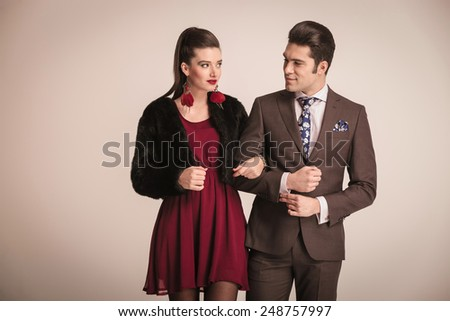 Beautiful young woman looking at her lover while she is holding his arm. He is looking at her while he is fixing his shirt. - stock photo