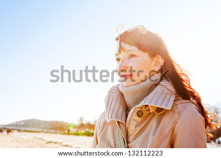 Beautiful young woman looking at the sky during a relaxing walk on the beach on a sunny day - stock photo