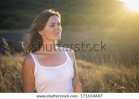Beautiful young woman looking at the view in a natural field with the golden light of the setting sun shinning onto her. - stock photo