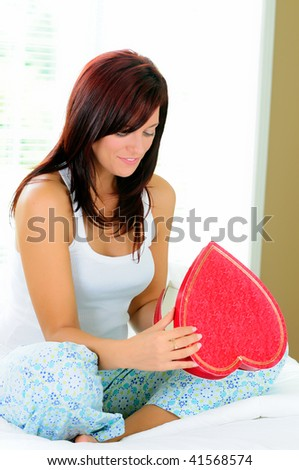 Beautiful Young Woman Looking Inside A Heart Shaped Box Of Chocolates - stock photo