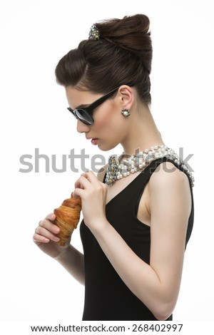 Beautiful young woman looking like audrey hepburn in sunglasses holding croissant - stock photo