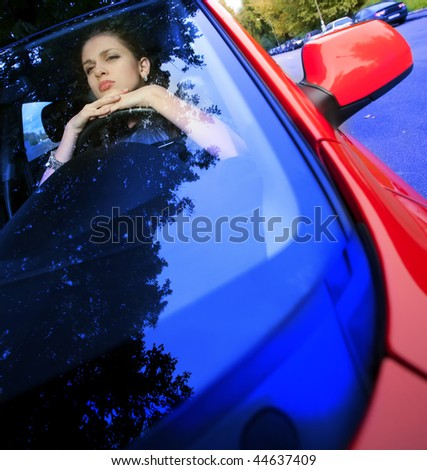 beautiful young woman looking through a car windshield - stock photo
