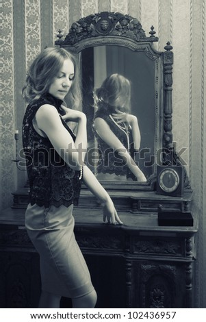 beautiful young woman looks at the reflection in the mirror in the - stock photo