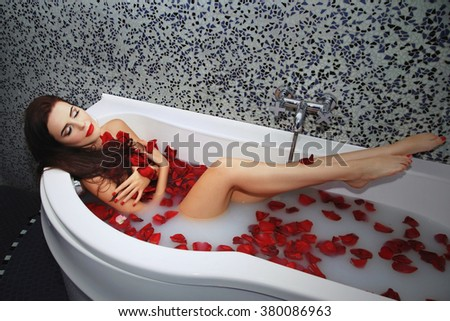 Beautiful young woman lying  in bath with eyes closed. Gets pleasure in warm water with rose petals - stock photo