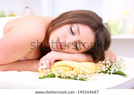 Beautiful young woman lying in spa salon close up - stock photo