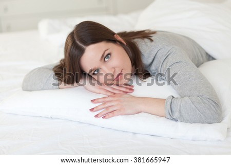 Beautiful young woman lying on a comfortable pillow, close up - stock photo