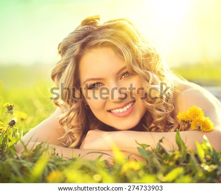 Beautiful Young Woman lying on a field, green grass and dandelion flowers. Outdoors Enjoy Nature. Healthy Smiling Girl lying in Green Grass - stock photo