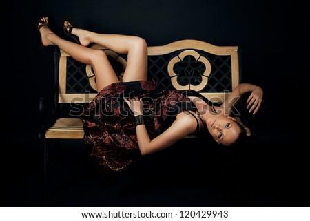 Beautiful young woman lying on bench - stock photo