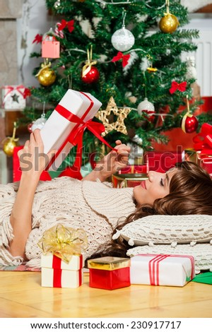 Beautiful young woman lying on carpet and opening Christmas present, in front of tree over living room - stock photo