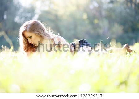 Beautiful Young Woman lying on grass reading - stock photo